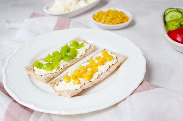 Pan tostado casero con queso cottage y aceitunas verdes, rodajas de col, tomate, maíz, pimiento verde en la tabla de cortar. concepto de comida sana, vista superior. lay flat