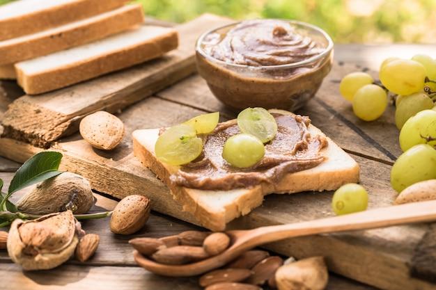 Pan tostado casero con uva y mantequilla de almendras en la mesa de madera para el desayuno. delicioso pan tostado listo para servir. pan tostado con crema para el desayuno.