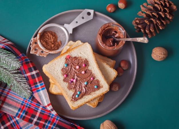 Pan tostado con crema de chocolate y mantequilla con árbol de navidad
