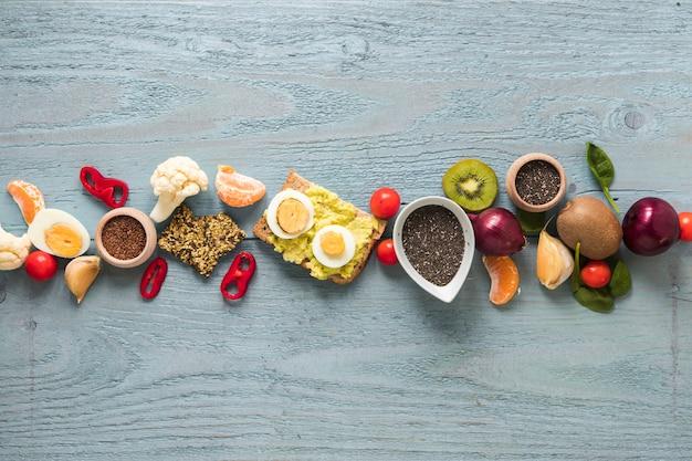Pan tostado; frutas frescas e ingredientes dispuestos en una fila en la mesa de madera