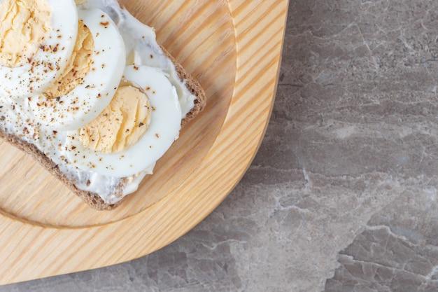 Pan tostado con huevos duros en placa de madera.