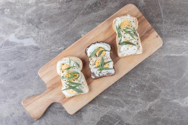 Pan tostado con huevos duros sobre tabla de madera.