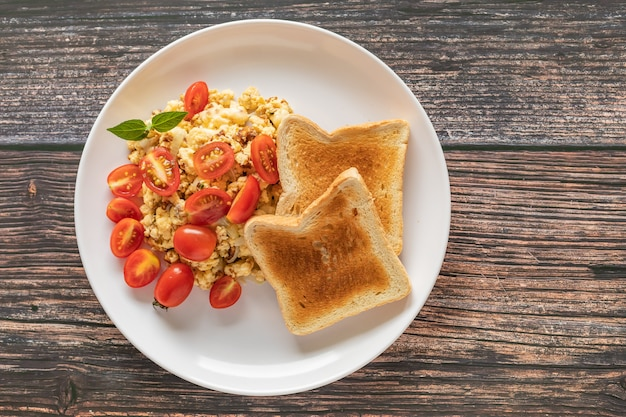 Pan tostado con huevos revueltos y tomate cherry