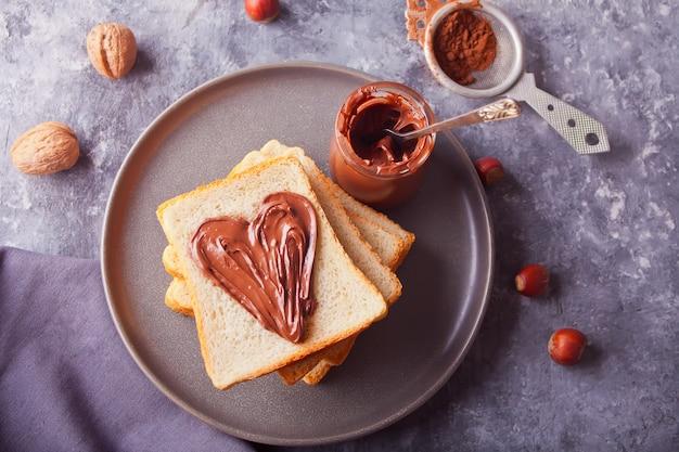 Pan tostado con mantequilla de crema de chocolate en forma de corazón, tarro de crema de chocolate