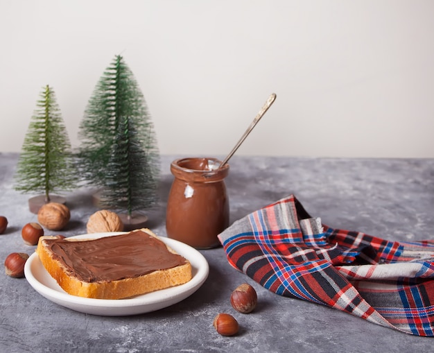 Pan tostado con mantequilla de crema de chocolate, juguetes de árboles de navidad en miniatura en el fondo de hormigón