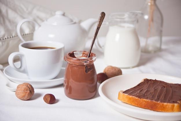 Pan tostado con mantequilla de crema de chocolate, una taza de café sobre el fondo blanco.