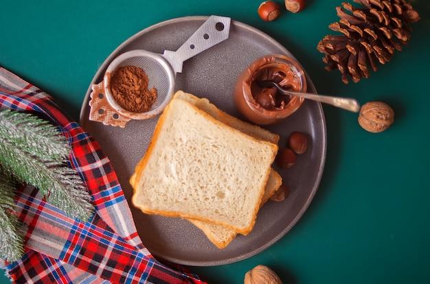 Pan tostado con mantequilla de crema de chocolate en el verde con decoración de navidad.