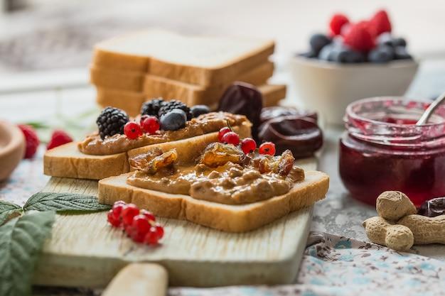 Pan tostado con mermelada casera de fresa y mantequilla de maní servida con bayas. pan tostado casero con mermelada y mantequilla de maní en la mesa de madera para el desayuno. delicioso pan tostado listo para servir.