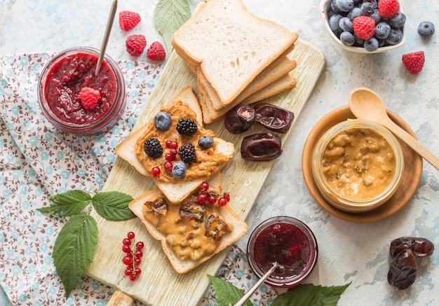Pan tostado con mermelada de fresa casera y mantequilla de maní servido con bayas. pan tostado casero con mermelada y mantequilla de maní en la mesa de madera para el desayuno.