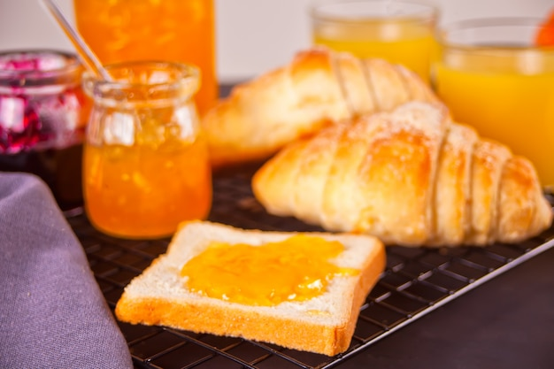 Pan tostado con mermelada de naranja, bollos de cruasanes recién hechos, vasos de jugo de naranja. concepto de desayuno.