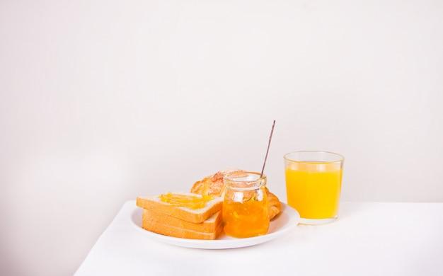 Pan tostado con mermelada de naranja, vaso de jugo de naranja sobre la mesa. concepto de desayuno.