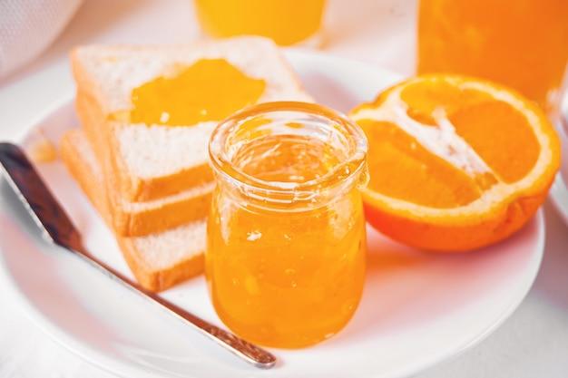 Pan tostado con mermelada de naranja, vasos de jugo de naranja sobre la mesa blanca. concepto de desayuno.