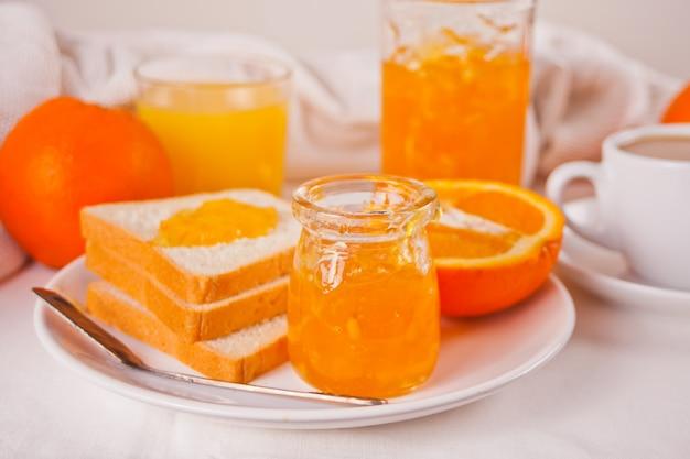 Pan tostado con mermelada de naranja, vasos de jugo de naranja en la superficie blanca concepto de desayuno.