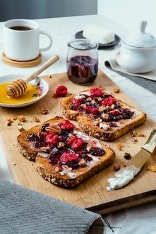 Pan tostado con miel, queso crema, mermelada de frutos rojos y café.