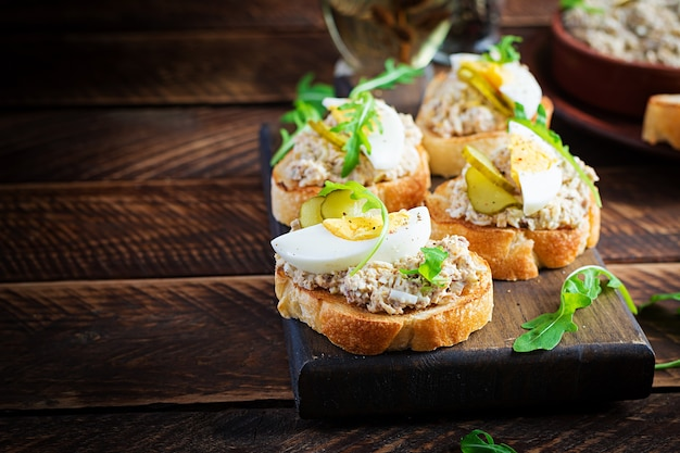 Pan tostado con mousse de bacalao salado sobre tabla de cortar de madera