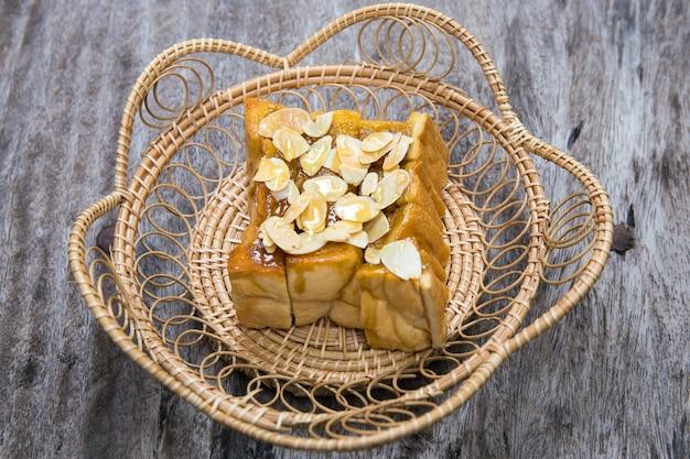 Pan tostado o pan verter miel con semillas de calabaza en mesa de madera