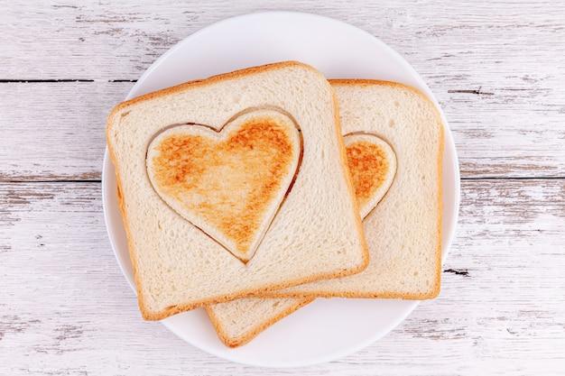 Pan tostado en rodajas corazones en mesa de madera, feliz desayuno familiar