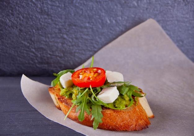 Pan tostado en rodajas con tomate, queso feta y rúcula en el papel
