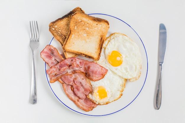 Pan tostado; tocino y medio huevos fritos en un plato de cerámica con un tenedor y un cuchillo de mantequilla aislados sobre fondo blanco