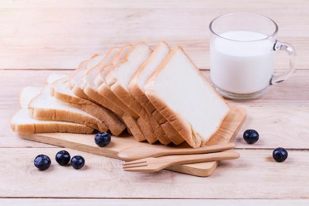 Pan tostado de trigo rebanado y leche de vaca en madera.