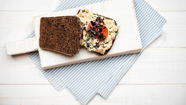 Pan tostado con verduras, pasta y tomates sobre tabla de madera