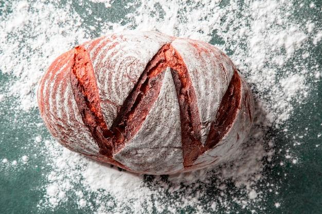 Pan tradicional dentro de la harina blanca en la mesa de piedra verde.