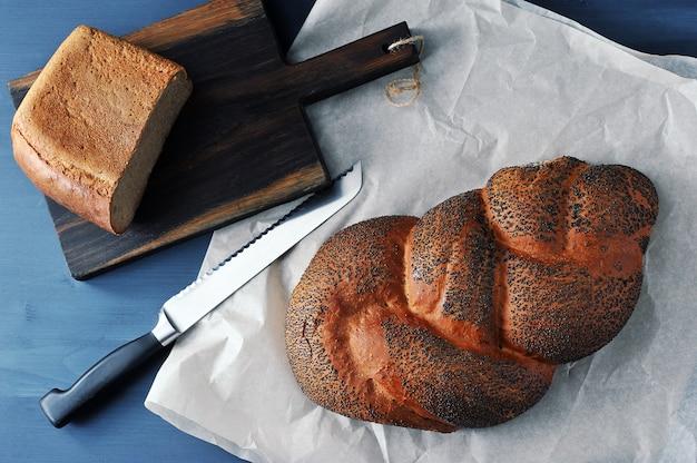 Pan trenzado con semillas de amapola en papel marrón con un cuchillo para el pan y la mitad del pan