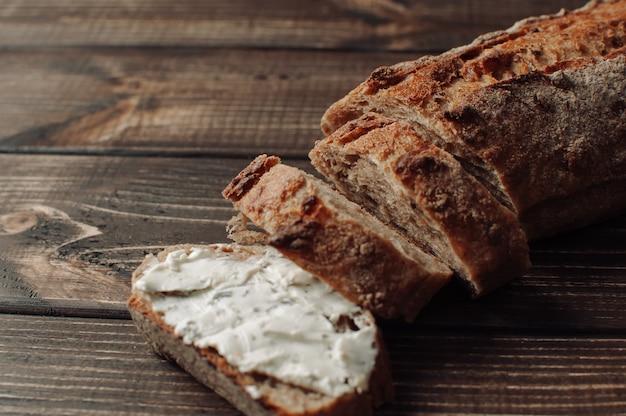 Pan de trigo sarraceno oscuro con sisam cubierto con queso cottage con hierbas en un corte sobre una mesa de madera en un estilo rústico.