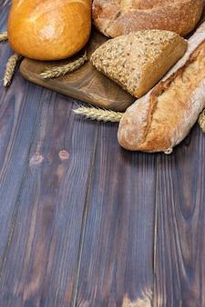 Pan y trigo sobre fondo de madera. vista superior con espacio de copia