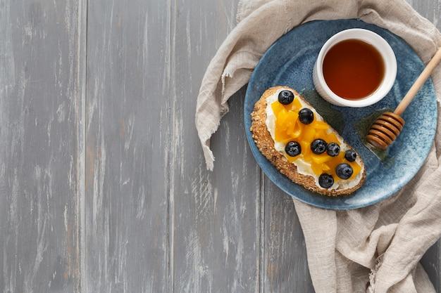 Pan de vista superior con queso crema y frutas en un plato con espacio de copia