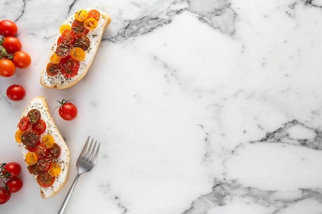 Pan de vista superior con queso crema y tomates cherry en mármol con espacio de copia