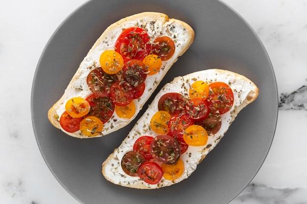Pan de vista superior con queso crema y tomates cherry en placa