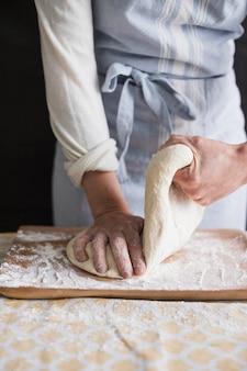 Una panadera que amasa la masa con harina en una tabla de cortar.