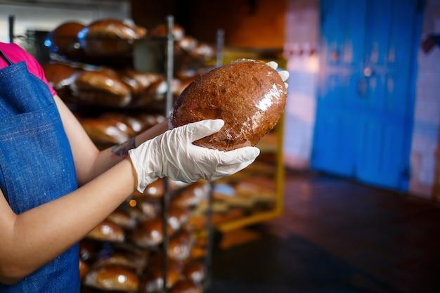 La panadera trabaja en una panadería. pan crujiente fresco de cerca