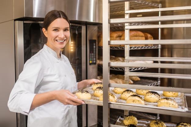 Panadería, bollos. feliz mujer bonita en uniforme blanco poniendo la bandeja de rollos en una rejilla especial para esperar a hornear en el horno