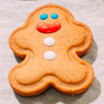 Panadería casera de navidad de cerca. fondo festivo del hombre de pan de jengibre sonriente en la hoja de cocción.