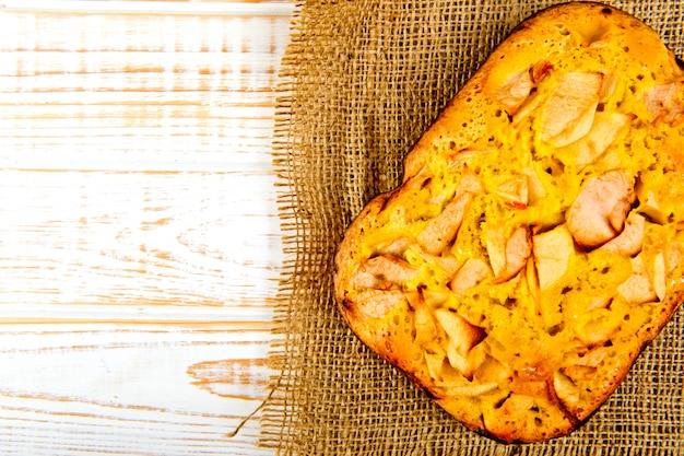 Panadería fresca. vista superior de pastel horneado con manzanas en cilicio sobre una madera blanca. estilo rústico