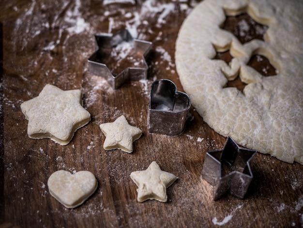 Panadería masa para galletas con molde de corte en la mesa de la cocina.