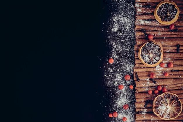 Panadería de navidad y año nuevo concepto. fondo de vacaciones con rodajas de cítricos de limón seco, conjunto de canela y vainilla en polvo. acogedora vacaciones de invierno para hornear, marco de vino caliente sobre fondo oscuro.