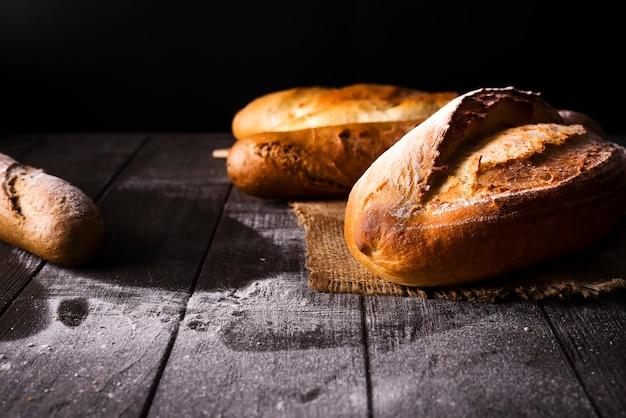 Panadería - panes y bollos crujientes rústicos del oro en fondo negro.