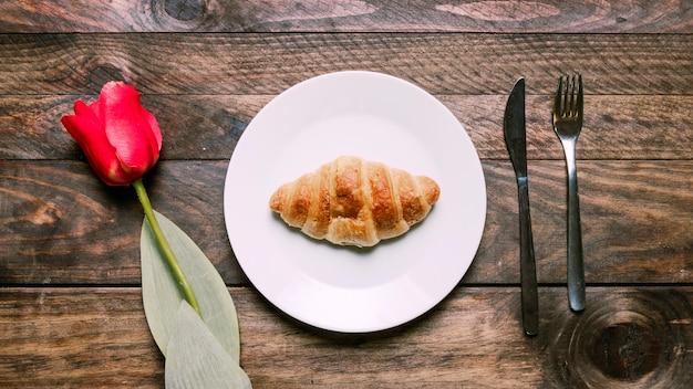 Panadería en un plato cerca de flores y cubiertos