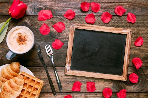 Panadería en un plato cerca de una taza de bebida, flores, cubiertos, pétalos y marco de fotos