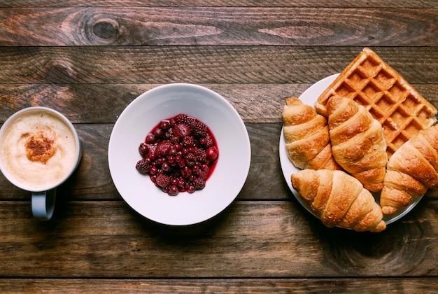 Panadería en un plato cerca de una taza de bebida y mermelada