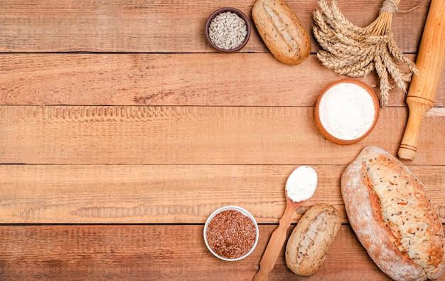 Panadería: varias hogazas de pan y bollos rústicos y crujientes, harina de trigo, un montón de espiguillas en tablas de madera.