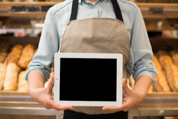 Panadería vendedor permanente mostrando tableta frente diferentes pasteles
