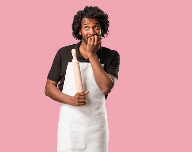 Panadero afroamericano guapo mordiéndose las uñas, nervioso y muy ansioso y asustado por el futuro, siente pánico y estrés.