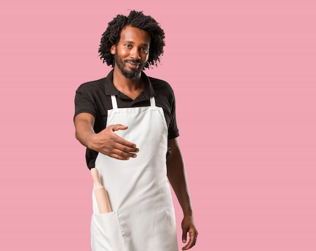 Panadero afroamericano guapo que se extiende para saludar a alguien o gesticular para ayudar