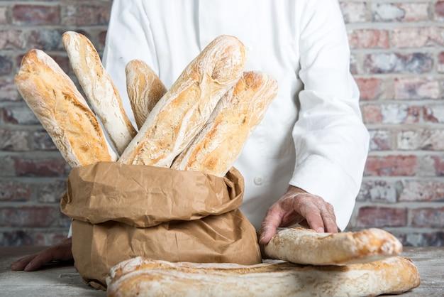 Panadero con baguettes francesas tradicionales
