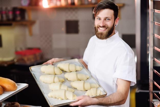 Panadero con barba prepara croissants para hornear y sonríe.