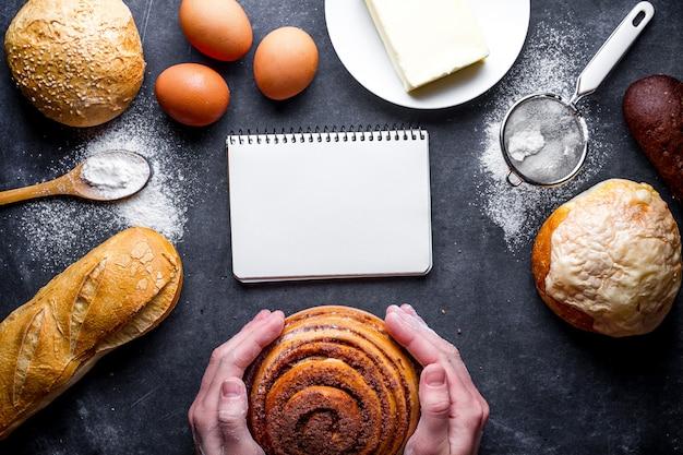 Panadero con bollo de canela casero fresco. diferentes productos de panadería frescos y crujientes en el fondo de pizarra negra.
